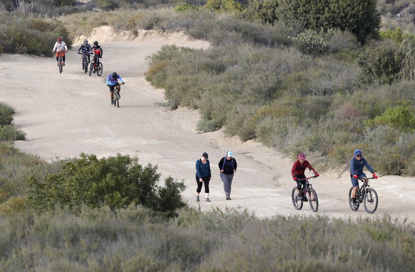 Mountain bikers and hikers climb a well-known trail at Top of the World in Laguna Beach on a recent afternoon.