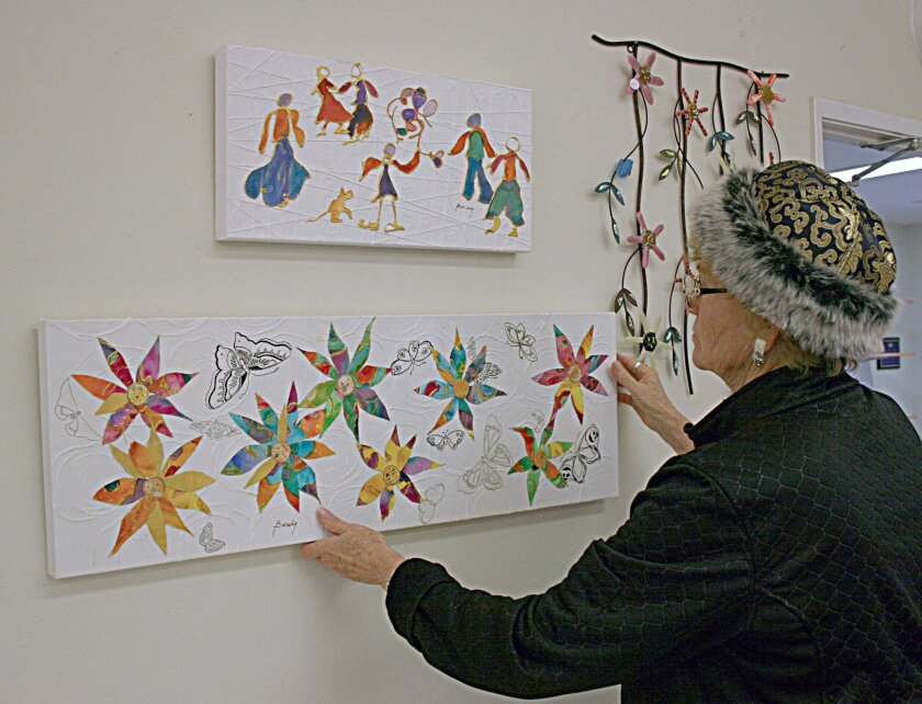 Flora Barwig, SDAG member, hangs two of her mixed media pieces on the wall of the Ecke Building, San Diego Botanic Garden.