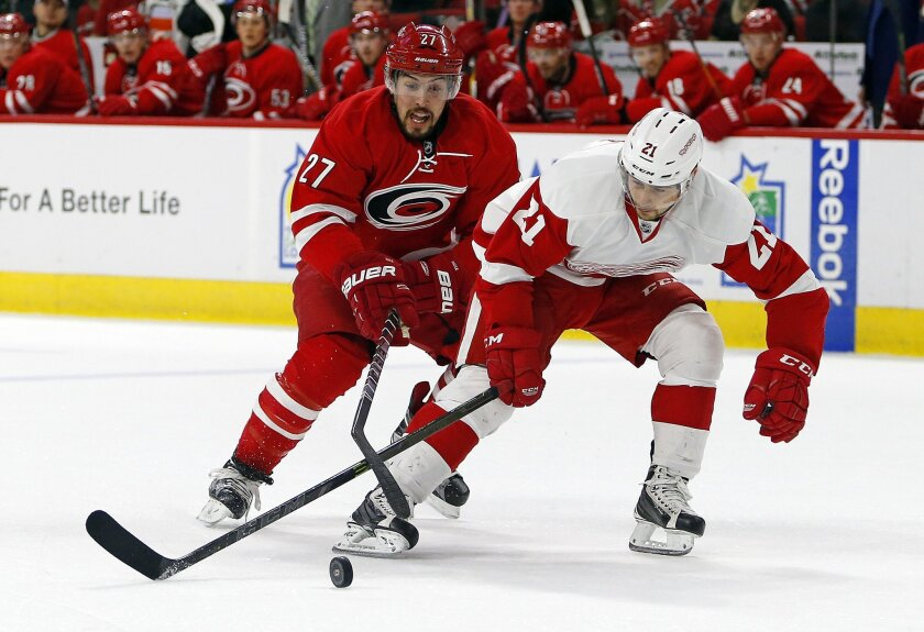 Carolina Hurricanes' Justin Faulk (27) tips the puck away from Detroit Red Wings' Tomas Tatar (21) during the first period of an NHL hockey game, Saturday, April 11, 2015, in Raleigh, N.C. (AP Photo/Karl B DeBlaker)