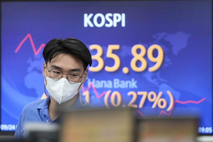 A currency trader walks by the screen showing the Korea Composite Stock Price Index (KOSPI) at a foreign exchange dealing room in Seoul, South Korea, Friday, Sept. 24, 2021. Asian shares were mixed Friday amid concerns over troubled Chinese real estate developer Evergrande and over the pandemic. (AP Photo/Lee Jin-man)