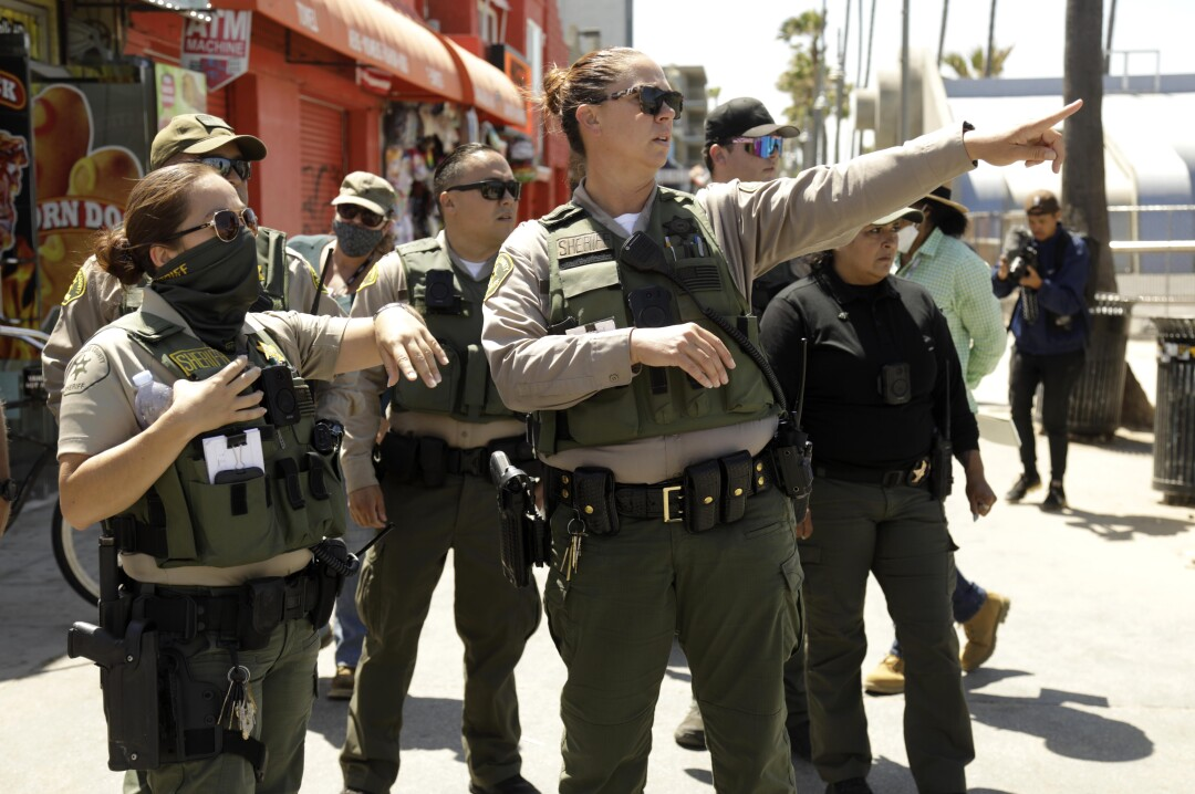 A group of sheriff's deputies gather on Ocean Front Walk in Venice.