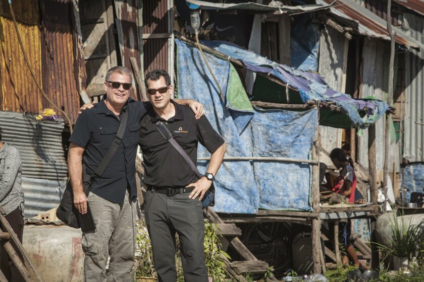 Pete Dupuis, left, and Sid Landolt, co-founders of World Housing, visit a makeshift home that their Philippines partner Gawad Kalinga hopes to replace with new construction.