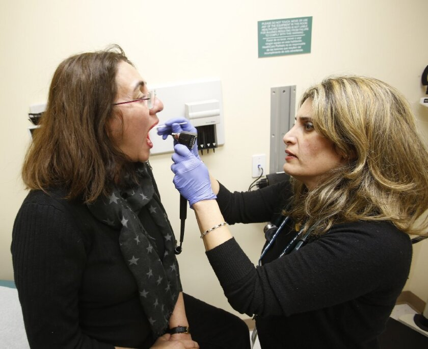 Last year's flu struck people between the ages of 50 and 64 harder than in years past. Here, Dr. Lina Sosoian collects a sample from patient Pari Tavakoli, 54, of Woodland Hills.