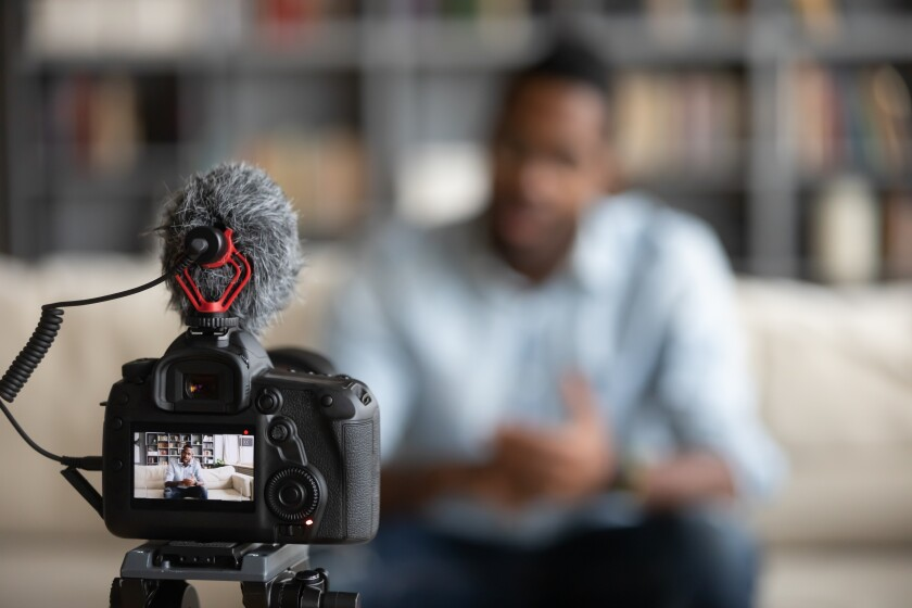 Stock photo of a Black tutor recording a video tutorial.