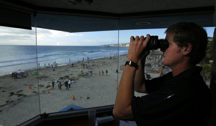 San Diego lifeguard Matt Sullivan looks out over La Jolla Shores where a great white shark was spotted earlier in the afternoon on Monday, July 2, 2012. The water was shut down to swimming and surfing due to the sighting.