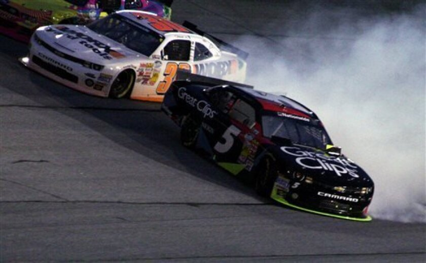 Driver Kasey Kahne (5) spins out in Turn 4 as Nelson Piquet Jr. (30) steers around him during the Nationwide Series auto race at Atlanta Motor Speedway, Saturday, Aug. 31, 2013, in Hampton, Ga. (AP Photo/Dale Davis)
