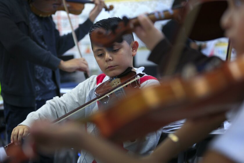 Isaac Valdez, 7, plays the violin during music practice Monday at Las Palmas School in National City. Isaac is part of the districtwide music program where school children gather three-times a week to practice mariachi.
