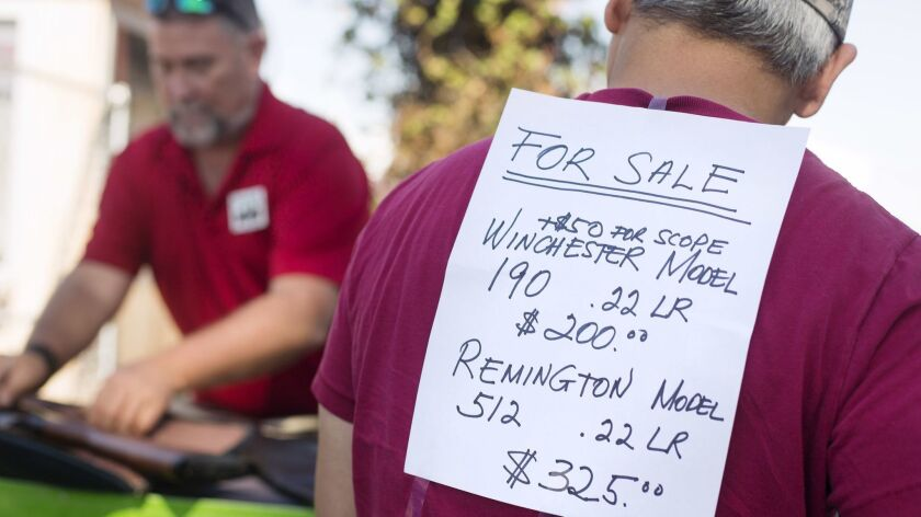 An attendee of the Crossroads of the West Gun Show advertises a gun for sale on his back at the OC F