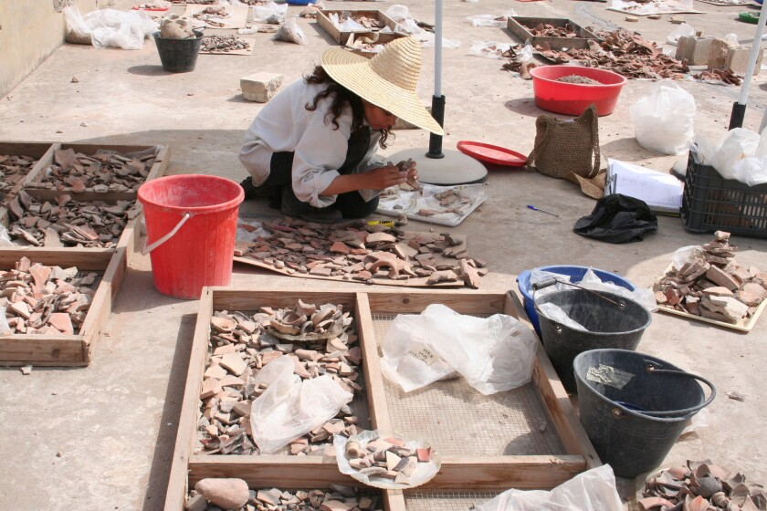 An archaeologist sorts pottery at the Sidon excavation site.