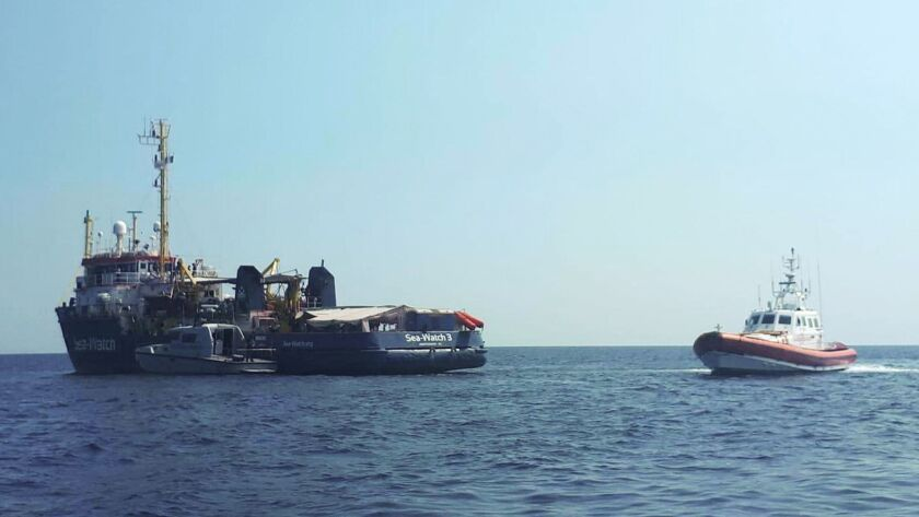 An Italian Coast Guard boat patrols next to the Sea-Watch 3 vessel, in the Mediterranean Sea just of