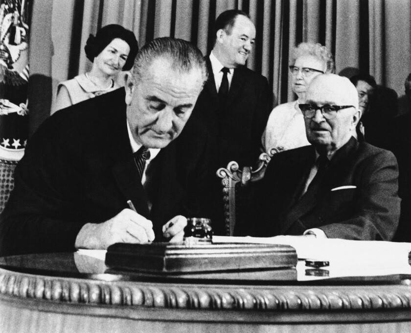 President Lyndon Johnson signed Medicare into law 50 years ago Thursday alongside former President Truman at a ceremony at the Truman Library in Independence, Mo. At rear are Lady Bird Johnson, Vice President Hubert Humphrey and former First Lady Bess Truman.
