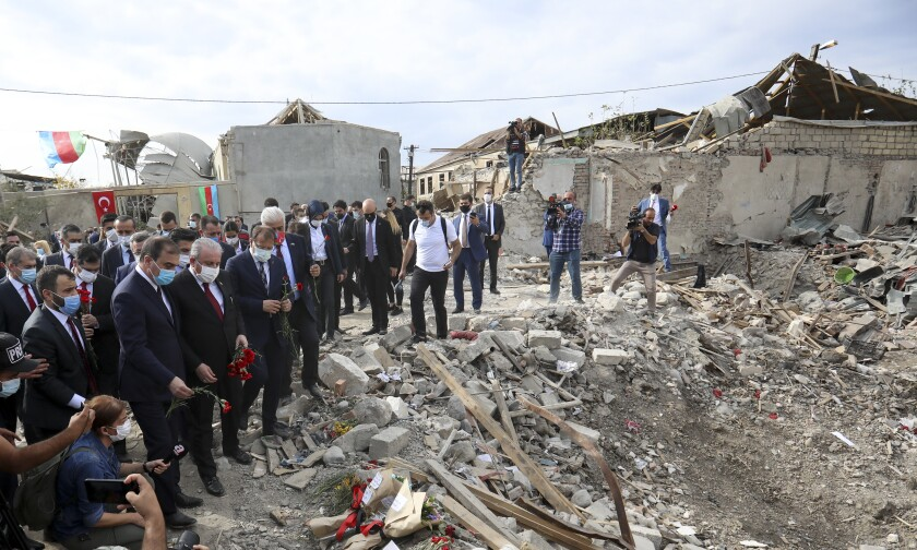 Turkey's Parliament Speaker Mustafa Sentop, third left, first row, visits a site of a destroyed houses in a residential area that was hit by rocket fire by Armenian forces, Tuesday, Oct. 20, 2020, in Ganja, Azerbaijan's second largest city, near the border with Armenia. (AP Photo/Aziz Karimov)