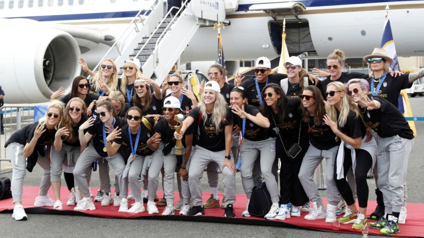 Members of the U.S. women's soccer team pose with the World Cup trophy Monday after arriving at Newark Liberty International Airport in New Jersey.