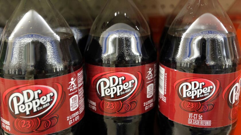 FILE - This April 28, 2016, file photo shows bottles of Dr. Pepper on a store shelf at Quality Cash