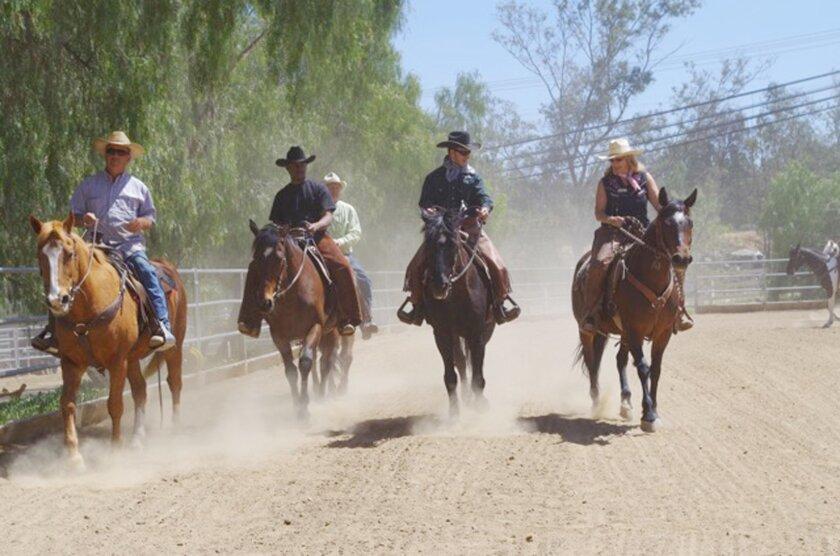 Ellen Gerkhe, right, gives some last-minute instruction to veteran Jay riding beside her. From left, wrangler K.L. Osborne, veteran Calvin and wrangler Larry Van help keep the pace.