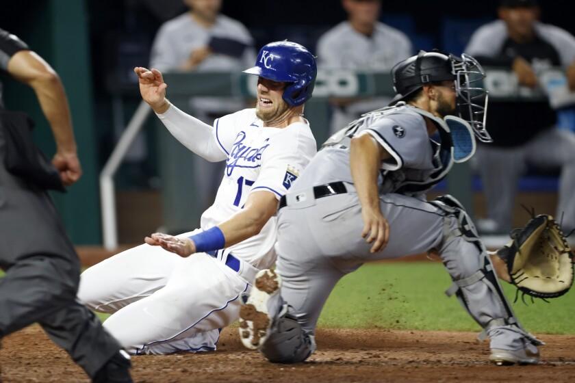 Kansas City Royals' Hunter Dozier, left, slides past Chicago White Sox catcher Seby Zavala to score the winning run in the 10th inning of a baseball game at Kauffman Stadium in Kansas City, Mo., Wednesday, July 28, 2021. (AP Photo/Colin E. Braley)
