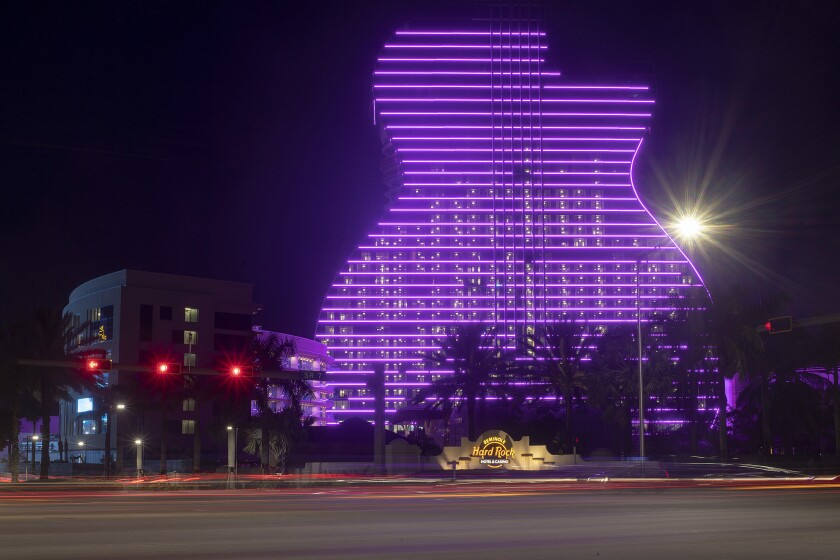 Cars drive on SR 7 in a time-lapse photograph in front of the new Guitar Hotel, at the Seminole Hard Rock Hollywood is illuminated, Wednesday, July 3, 2019.