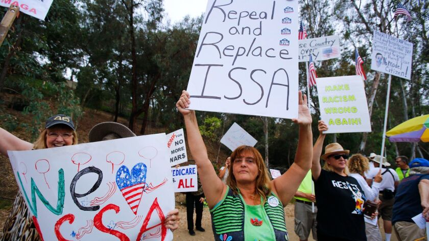 Costa del Sol of Vista holds an anti-Congressman Darrell Issa sign next to a Issa supporter during the weekly rally outside the congressman's office in vista.