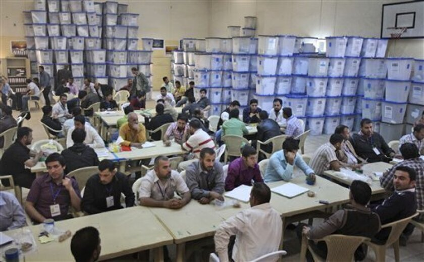Electoral workers sit with piles of ballot boxes at a counting center in Baghdad, Iraq, Monday, March 8, 2010. The conclusion of Sunday's vote does not spell an immediate end to Iraq's political uncertainty, as it could be days until results come in and with the fractured nature of Iraqi politics, months to form a government. (AP Photo/Karim Kadim)