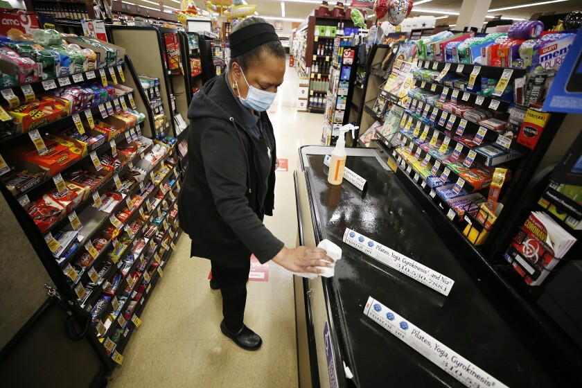 Vons checker cashier Miyoshi Lampkin, who has worked at Vons for 40 years, cleans and sanitizes her checkout lane.