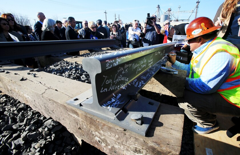 Invited guests sign segments of railroad track during a groundbreaking ceremony for the bullet train station in Fresno.
