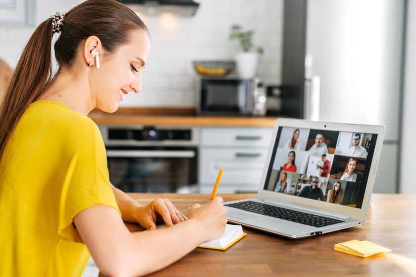 Side view of young woman watching on laptop display