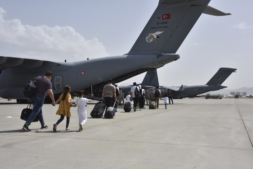 People walk to military planes.