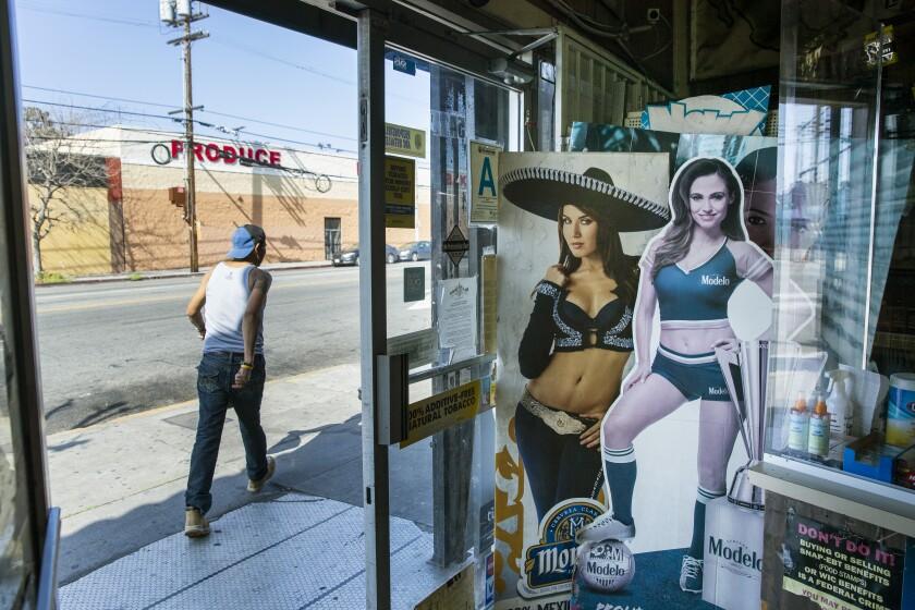 WEST ADAMS, CA - APRIL 04: A customer leaves the Royal Liquor Mart on Saturday, April 4, 2020 in West Adams, CA.