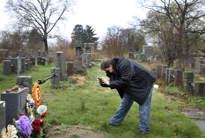 Brian Walter takes a photograph of his late father's gravestone at the All Faiths Cemetery in the Queens borough of New York, Sunday, April 11, 2021. John Walter died from the coronavirus May 10, 2020. (AP Photo/Jessie Wardarski)
