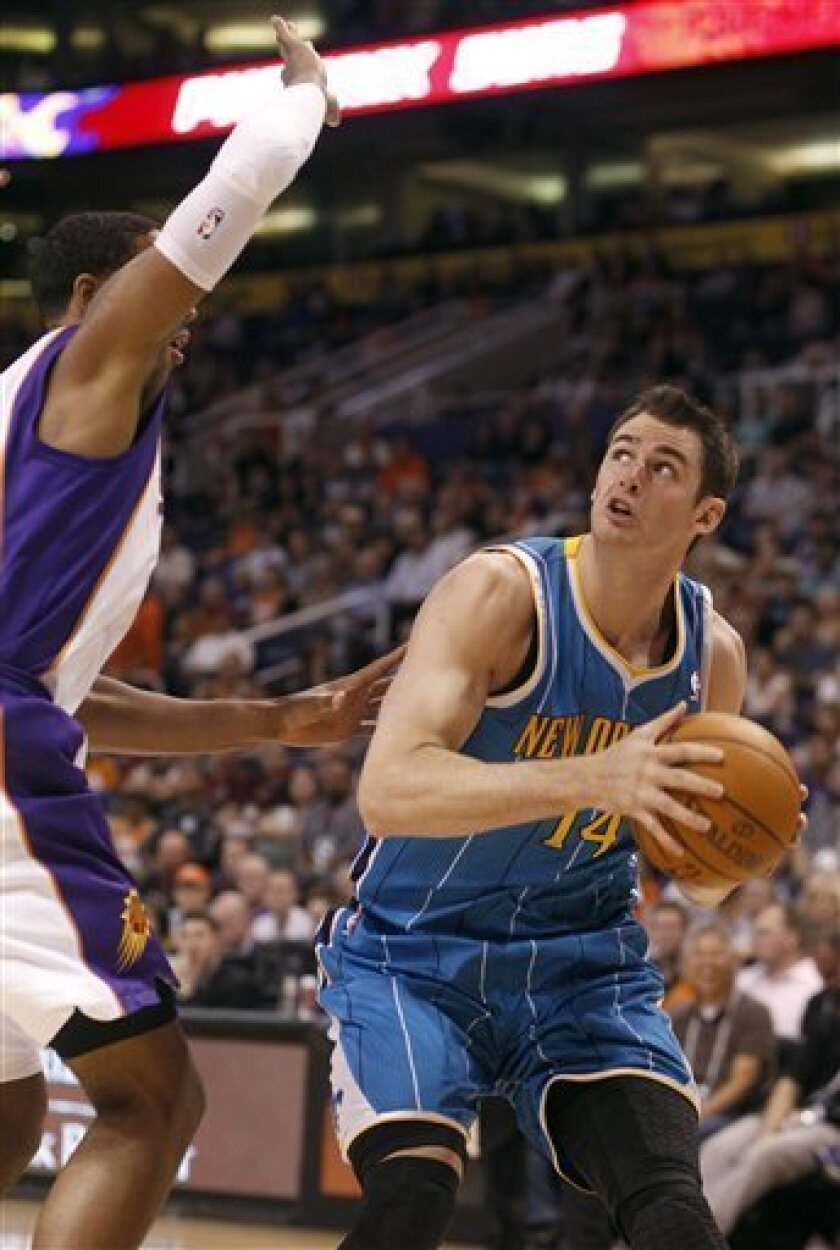 New Orleans Hornets center Jason Smith, right, looks up to the basket as he is covered by Phoenix Suns forward Channing Frye, left, in the first quarter of an NBA basketball game Sunday, April 1, 2012, in Phoenix.(AP Photo/Paul Connors)