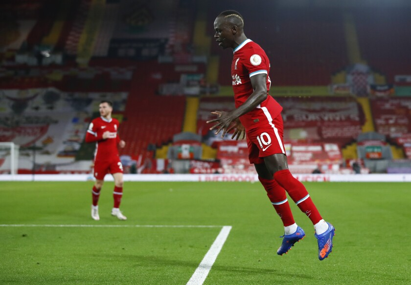Liverpool's Sadio Mane celebrates after scoring his team's first goal during the English Premier League soccer match between Liverpool and Arsenal at Anfield in Liverpool, England, Monday, Sept. 28, 2020. (Jason Cairnduff/Pool via AP)