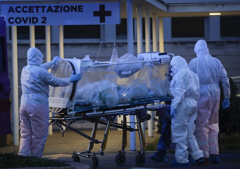 "A patient in a biocontainment unit is carried on a stretcher at the Columbus Covid 2 Hospital in Rome, Monday, March 16, 2020. The new Columbus Covid 2 Hospital, an area fully dedicated to the COVID-19 cases at the Gemelli university polyclinic, opened today with 21 new ICU units and 32 new beds, in order to support the regional health authorities in trying to contain the pandemic. Sign at top in Italian reads ""Admission COVID 19"". For most people, the new coronavirus causes only mild or moderate symptoms. For some it can cause more severe illness, especially in older adults and people with existing health problems. (AP Photo/Alessandra Tarantino)"
