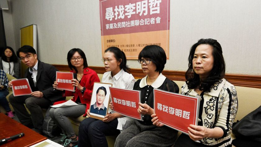 Lee Ching-yu, third from right, holds a photo of her missing husband and pro-democracy activist Lee Ming-che on March 24, 2017, during a news conference in Taipei, Taiwan, with representatives of nongovernmental organizations.