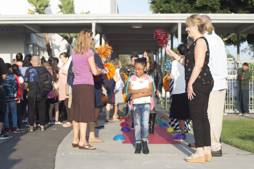 Flanked by cheering school staff, students and their families walk down a red carpet Tuesday to start the first day of school at College Park Elementary School in Costa Mesa.