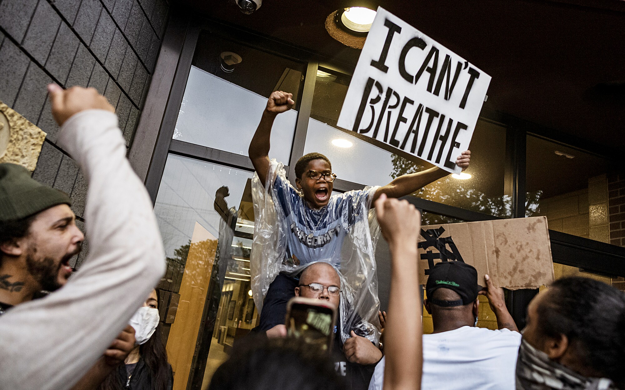 People gather at a Minneapolis police precinct during a protest May 26 after the death of George Floyd, who told the officer kneeling on his neck that he couldn't breathe.