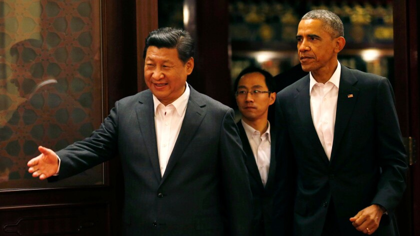 President Barack Obama is shown the way by China's President Xi Jinping as they enter a room for a meeting in Beijing on Nov. 11, 2014.