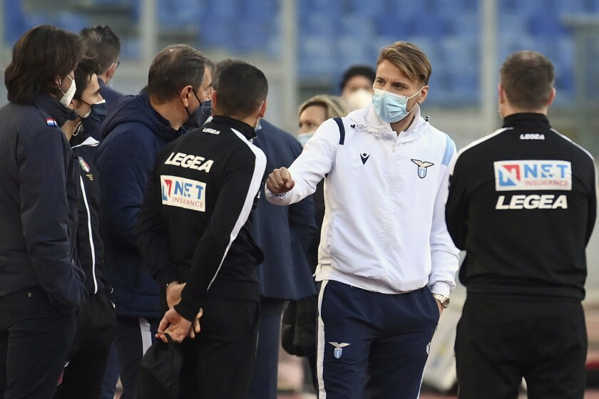 Lazio's Ciro Immobile, 2nd from right, stands on the pitch prior to the Serie a soccer match between Lazio and Torino, at the Rome Olympic Stadium Tuesday, March 2, 2021. Lazio walked out into Stadio Olimpico for its Serie A match on Tuesday even though it knows its Torino opponents are still in Turin. A coronavirus outbreak forced Torino players and staff into self-isolation that doesn't end until midnight Tuesday, hours after the scheduled kickoff against Lazio in Rome. (Alfredo Falcone/LaPresse via AP)