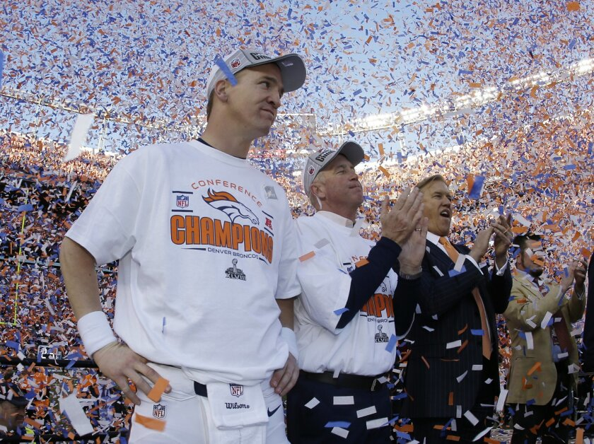 Denver Broncos quarterback Peyton Manning, stands with Broncos' head coach  John Fox and Broncos VP John Elway during the trophy ceremony after the AFC Championship NFL playoff football game in Denver, Sunday, Jan. 19, 2014. The Broncos defeated the Patriots 26-16 to advance to the Super Bowl. (AP
