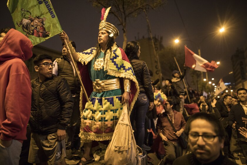 A supporter of Peruvian President Martin Vizcarra is dressed as an Inca protest against lawmakers outside Congress after Vizcarra dissolved the legislature in Lima, Peru, Monday, Sept. 30, 2019. Opposition legislators defied Vizcarra's order dissolving congress by voting to suspend him from office and swearing in Vice President Mercedes Araoz as the South American nation's new leader. (AP Photo/Rodrigo Abd)