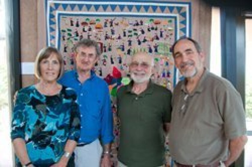 From left: Nancy Harmon, Roger Harmon, Irving Himelblau and Bob Montgomery stand in front of a Hmong story cloth.  Photo: Claire Harlin
