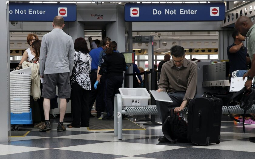 Travelers pass through a Transportation Security Administration checkpoint at O'Hare International Airport, Friday, May 27, 2016, in Chicago. Memorial Day weekend, the unofficial start of summer vacations for many and a busy travel period, serves as a crucial test for the TSA. (AP Photo/Kiichiro Sa