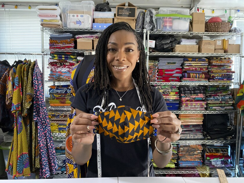 """Iguehi James, an Oakland, Calif., fashion entrepreneur, holds a face mask she designed for her apparel company Love Iguehi on Tuesday, Sept. 15, 2020. She received a $5,000 grant from the Oakland African American Chamber of Commerce's """"Resiliency Fund,"""" which seeks to help Black-owned businesses stay afloat during the coronavirus pandemic. (AP Photo/Terry Chea)"""