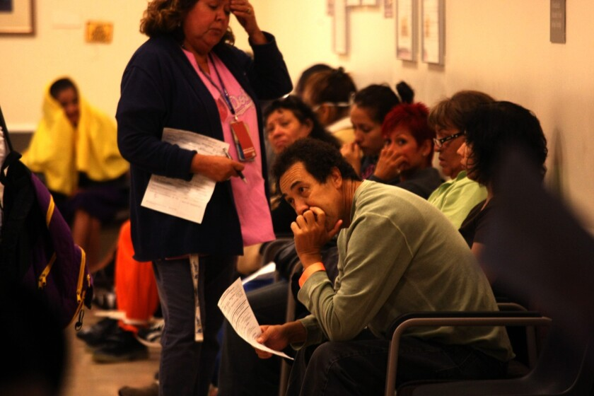 Patients wait for treatment at the Los Angeles County-USC Medical Center emergency room last October. A health official said L.A. County public hospitals are benefiting from an uptick in insured patients since the implementation of the federal Affordable Care Act this year.