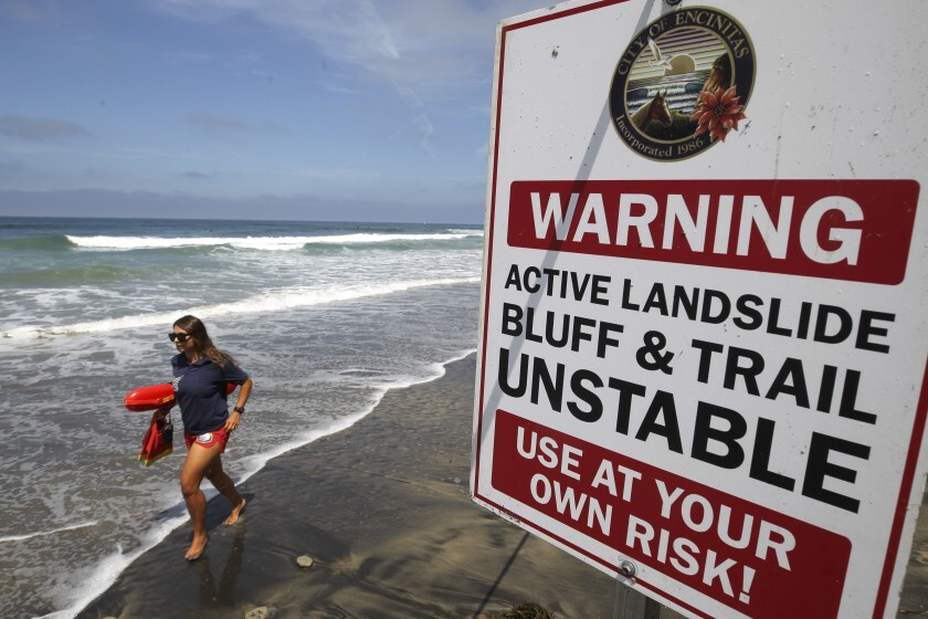 A lifeguard runs past one of several warning signs posted next to the area of the fatal bluff collapse in Encinitas.