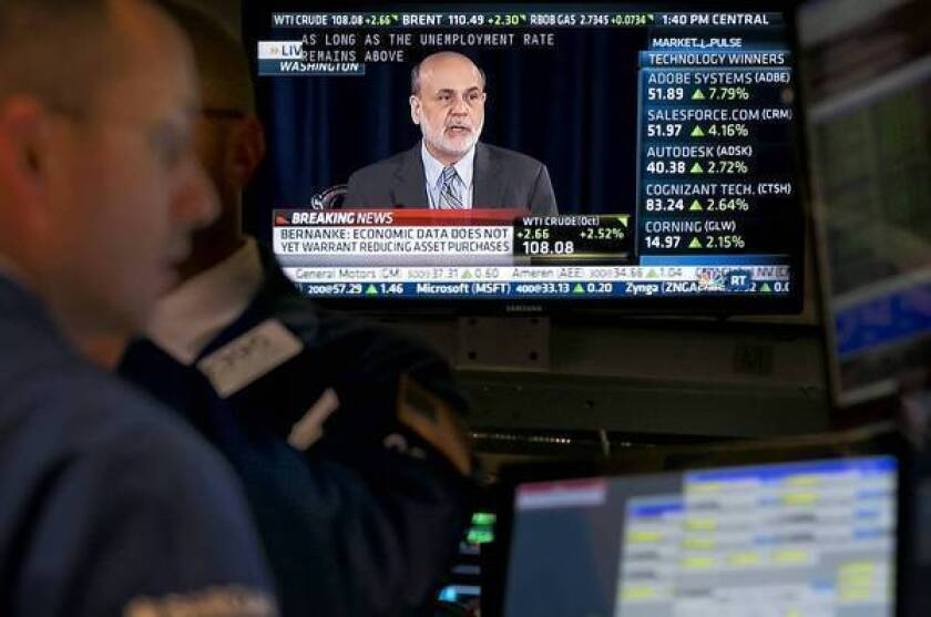 Federal Reserve Chairman Ben S. Bernanke's televised news conference Wednesday is shown at the New York Stock Exchange. He defended the Fed's surprise move.