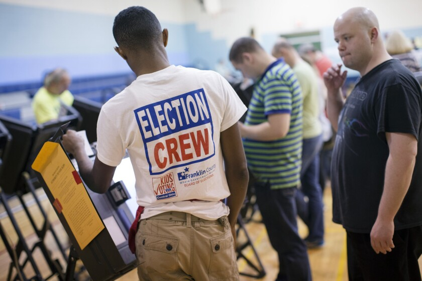 Trayvon Thompson, 17, left, helps a voter use an electronic voting machine at the Schiller Recreation Center polling station Tuesday in Columbus, Ohio. Voters in Ohio are deciding whether to legalize the recreational use of marijuana.