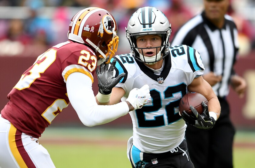 Carolina Panthers running back Christian McCaffrey tries to fend off Washington's Quinton Dunbar during a game in October 2018.