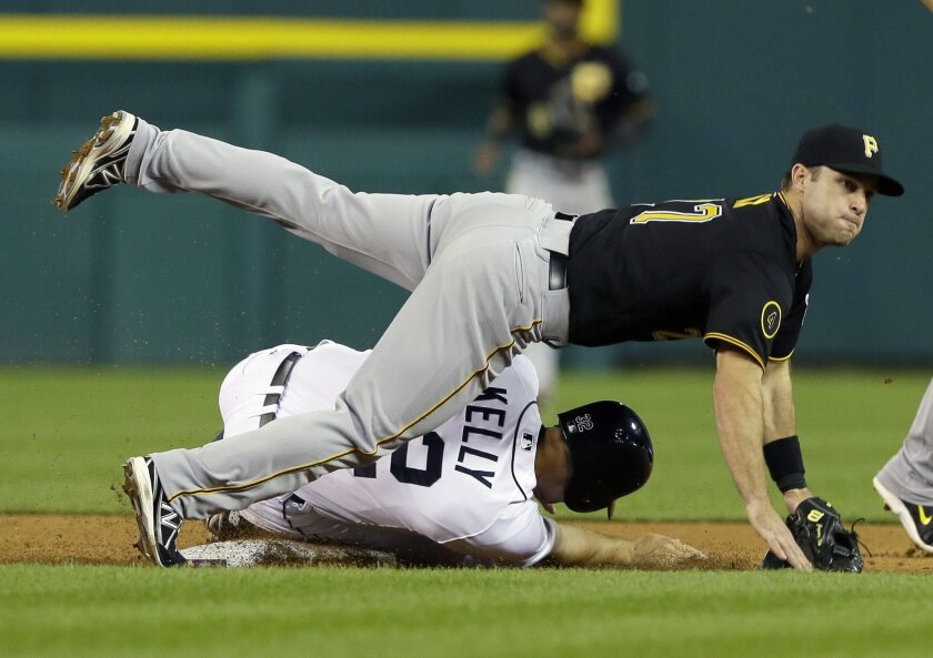 Pittsburgh Pirates second baseman Jayson Nix falls over Detroit Tigers' Don Kelly after throwing to first for the out on Tigers' runner Nick Castellanos during the seventh inning of an interleague baseball game, Wednesday, Aug. 13, 2014 in Detroit. (AP Photo/Carlos Osorio)