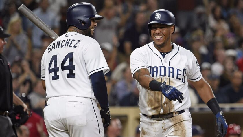 Yangervis Solarte of the San Diego Padres, right, is congratulated by Hector Sanchez after scoring during the fifth inning of a game against the Philadelphia Phillies at Petco Park on Aug. 15, 2017, in San Diego.