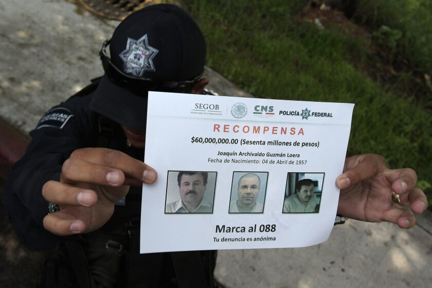 "A police officer shows a reward notice on July 16 as members of Mexico's Federal Police continue investigating the escape of drug trafficker Joaquin ""El Chapo"" Guzman."